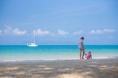 Le père et la fille dans le costume de natation jouent sur la plage d'océan avec le ya Images libres de droits