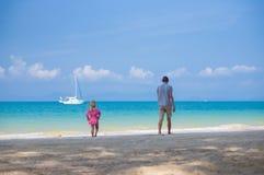 Le père et la fille dans le costume de natation jouent sur la plage d'océan avec le ya Photographie stock