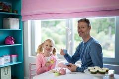 Le père et la fille jouant un rôle de service à thé jouent Image stock