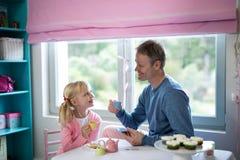 Le père et la fille jouant un rôle de service à thé jouent Images libres de droits
