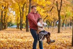 Le père et la fille jouent et ont l'amusement en parc de ville d'automne Ils posant, sourire, jouant Arbres jaunes lumineux image libre de droits