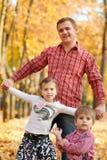 Le père et la fille jouent et ont l'amusement en parc de ville d'automne Ils posant, sourire, jouant Arbres jaunes lumineux images libres de droits