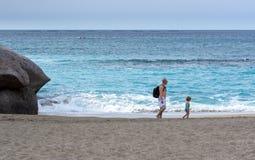 Le père et la fille marchent le long de la plage sablonneuse de la ville d'Adeje sur l'île de Ténérife, envergure Photographie stock libre de droits