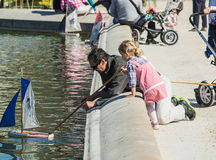 Le père et la fille poussent le voilier de jouet dans la fontaine au jardin du Luxembourg, Paris, France Photos libres de droits