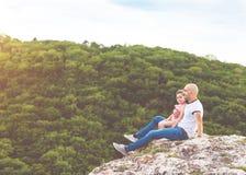 Le père et la fille s'asseyant sur la montagne basculent photos libres de droits