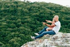 Le père et la fille s'asseyant sur la montagne basculent photographie stock libre de droits