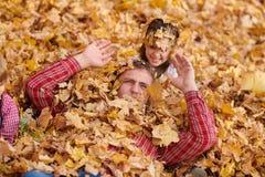 Le père et la fille se trouvent sur les feuilles jaunes et ont l'amusement en parc de ville d'automne Ils posant, sourire, jouant photos stock