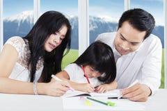 Le père et la mère aident leur enfant pour l'étude Images stock