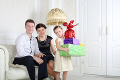 Le père et la mère s'asseyent au sofa et à la fille avec des cadeaux Photo libre de droits