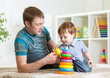 Le père et le bébé garçon jouent ensemble d'intérieur à la maison image stock