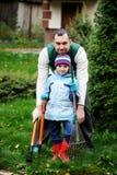 Le père et le descendant travaillant en automne font du jardinage Photos stock