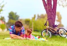 Le père et le fils détendant après bicyclette montent en parc de ville Photos stock
