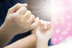 Le père et le fils de plan rapproché tiennent des mains avec amour Photographie stock