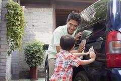 Le père et le fils de sourire nettoient leur monospace ensemble images stock