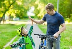 Le père et le fils donnent la haute cinq tout en faisant un cycle en parc Images stock