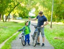 Le père et le fils donnent la haute cinq tout en faisant un cycle en parc Photo stock