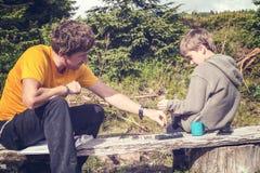 Le père et le fils jouent aux échecs tout en détendant dans le camp Images stock