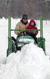 Le père et le fils labourent une commande neigeuse sur un tracteur Photos libres de droits