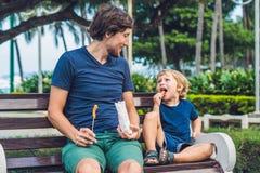 Le père et le fils mangent les patates douces frites en parc Concept de nourriture industrielle Photo stock