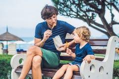 Le père et le fils mangent les patates douces frites en parc Nourriture industrielle c Photos libres de droits