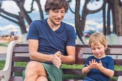 Le père et le fils mangent les patates douces frites en parc Nourriture industrielle c Photo stock