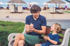 Le père et le fils mangent les patates douces frites en parc Nourriture industrielle c Photo libre de droits