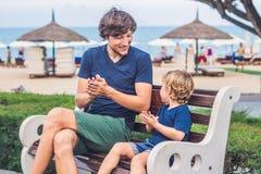 Le père et le fils mangent les patates douces frites en parc Nourriture industrielle c Images stock
