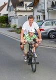 Le père et le fils montent sur un BMX, ayant l'amusement Photo stock