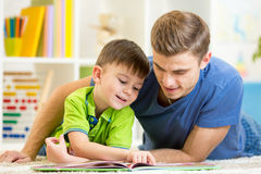Le père et le fils ont lu se reposer ensemble sur le plancher image stock