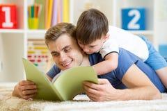 Le père et le fils ont lu un livre sur le plancher à la maison images stock