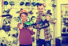 Le père et le fils que l'apparence les fait du patin à roulettes ont acheté dans le magasin de sports Photos stock