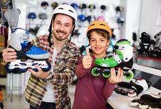 Le père et le fils que l'apparence les fait du patin à roulettes ont acheté dans le magasin de sports Photographie stock
