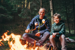 Le père et le fils rôtissent des sucreries de guimauve sur le feu de camp dans l'avant image stock