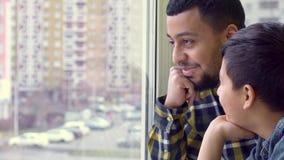 Le père et le fils regardent la fenêtre banque de vidéos