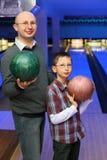 Le père et le fils retient des billes pour le bowling Photo stock