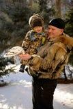 Le père et le fils sont venus au parc pour alimenter des titmouses et des pigeons Images stock