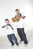 Le père et le fils visant avec des guitares aiment des armes à feu Photographie stock libre de droits