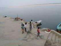 Le père et les enfants démêlent le filet de pêche près d'Assi Ghat Varanasi India photos libres de droits