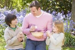 Le père et les enfants sur Pâques recherchent des oeufs Photo libre de droits