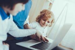 Le père et les fils observe une vidéo sur l'ordinateur portable photo libre de droits