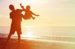 Le père et les petites silhouettes de fils jouent au coucher du soleil Photos stock