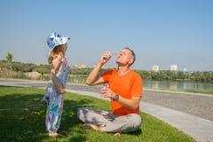 Le père et sa petite fille gonflent attentivement des bulles de savon Image libre de droits