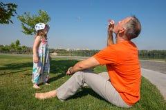 Le père et sa petite fille gonflent des bulles orientation vers des numéros inférieurs et moyens Photos stock