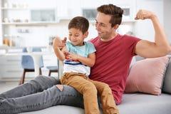 Le père et son petit fils comparent la taille de leur biceps Photos libres de droits