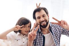 Le père heureux avec le fils montre le signe de la victoire photos libres de droits