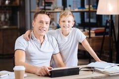 Le père heureux et le fils posant dans les pères étudient Images libres de droits