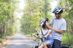 Le père heureux et la fille faisant un cycle en parc porte un casque de bicyclette à sa fille image libre de droits