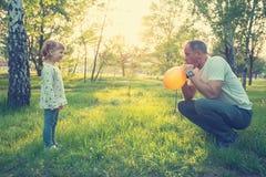 Le père heureux et la petite fille de sourire soufflent BAL coloré Photographie stock
