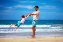 Le père heureux et le fils enthousiastes ayant l'amusement sur la plage d'été, apprécient la vie Photos libres de droits