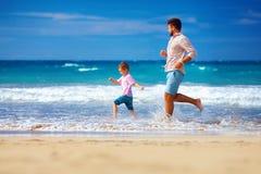 Le père heureux et le fils enthousiastes courant l'été échouent, apprécient la vie Images stock